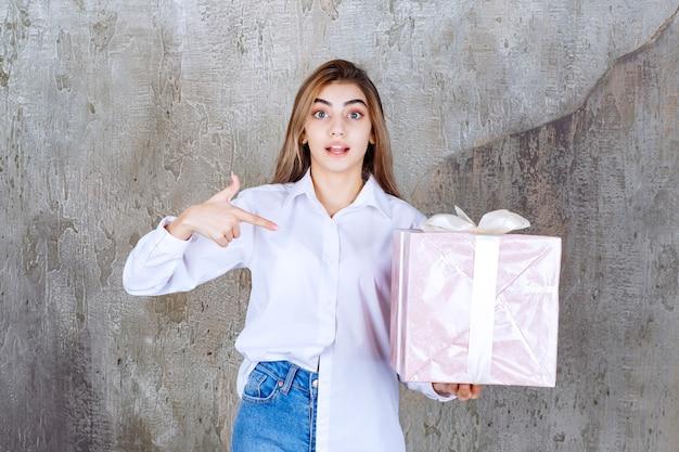 白いリボンで包まれたピンクのギフトボックスを保持している白いシャツの女性。