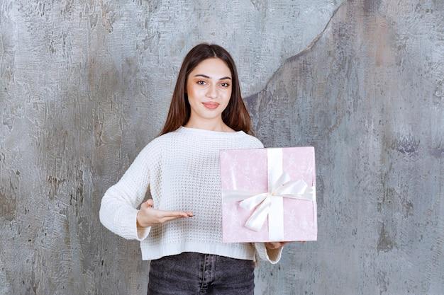 보라색 선물 상자를 들고 흰 셔츠에 여자.