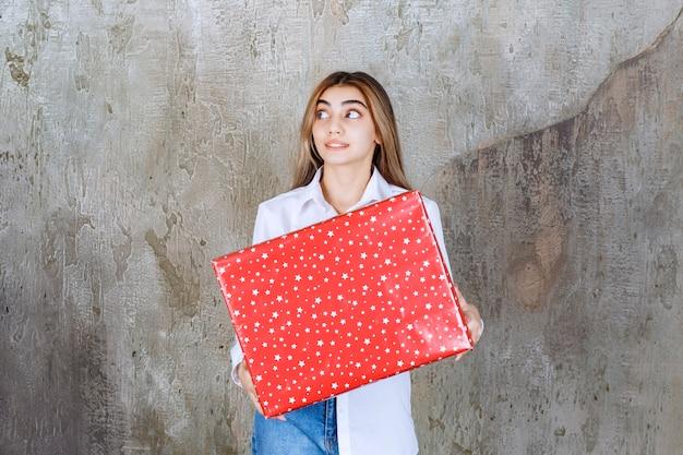 白い点が付いた赤いギフトボックスを持っている白いシャツを着た女性は、混乱して思慮深く見えます。