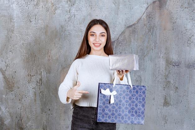 銀のギフトボックスと青い買い物袋を保持している白いシャツの女性。