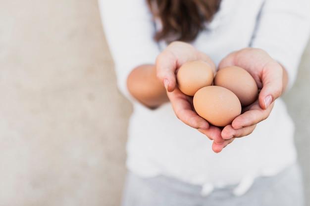 彼女の手で茶色の卵を保持している白いシャツの女性