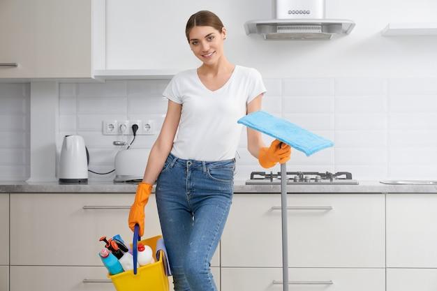 Женщина в белой рубашке держит моющее средство для чистки
