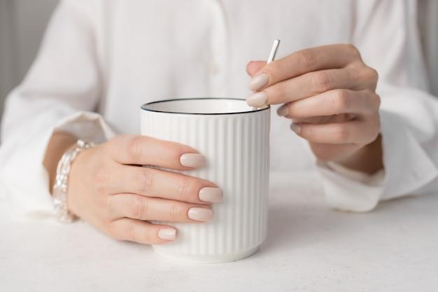 Женщина в белой рубашке, держащая белую кружку утреннего уюта, концепция релаксации