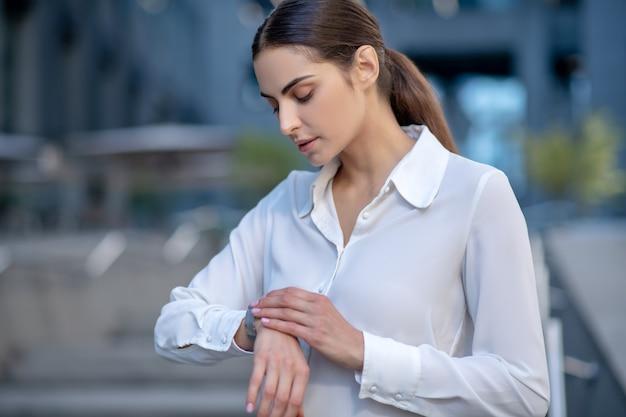 Женщина в белой рубашке смотрит на умные часы