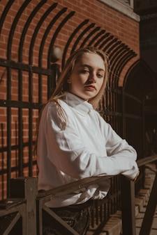 Женщина в белой рубашке на деревянном заборе