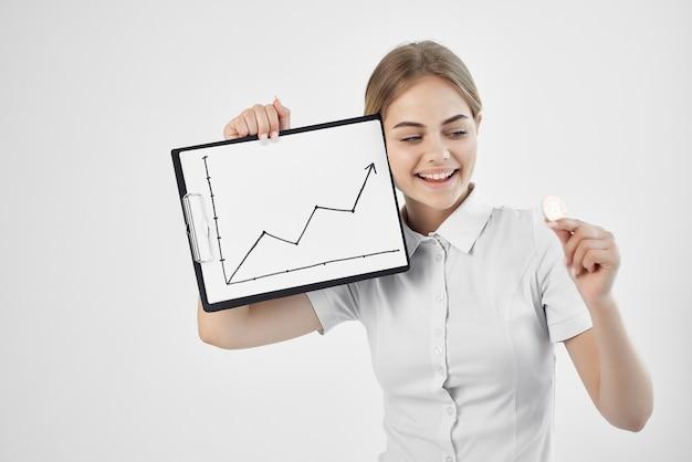 暗号通貨ビットコインを上げる白いシャツの女性