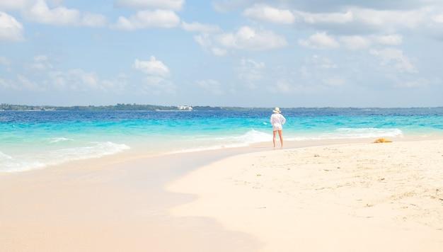 Женщина в белой рубашке стоит на берегу и смотрит на океан