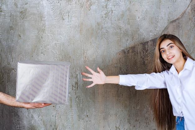 콘크리트 벽에 서있는 흰 셔츠를 입은 여인은 은색 선물 상자와 그것을 가져갈 갈망하는 손을 제공 받고 있습니다.