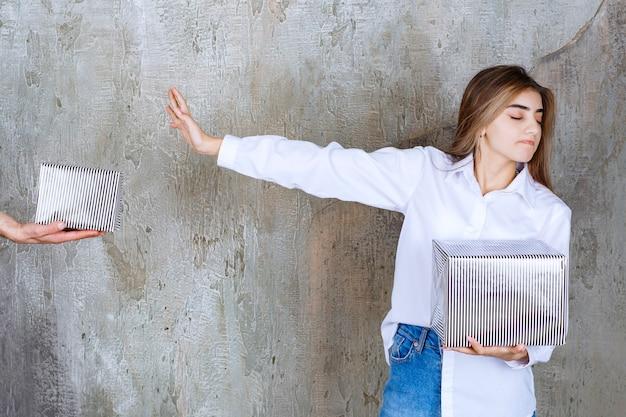 콘크리트 벽에 서있는 흰 셔츠를 입은 여자는 은색 선물 상자를 제공하고 그것을 거부합니다.