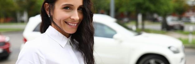 白いシャツの女性は通りと笑顔に立っています。肯定的な感情の毎日のコンセプト。