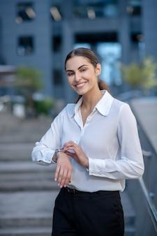 Женщина в белой рубашке трогает умные часы и улыбается