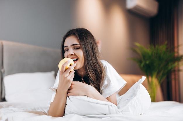 Женщина в белой шелковой пижаме кусает яблоко или персик. женская модель с фруктами в руках, лежа на кровати. утром или вечером в спальне со здоровым завтраком или ужином в постели.