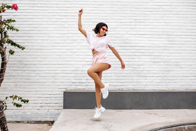 通りにジャンプする白いスニーカーの女性。夏を楽しむ踊る女性の全身像。