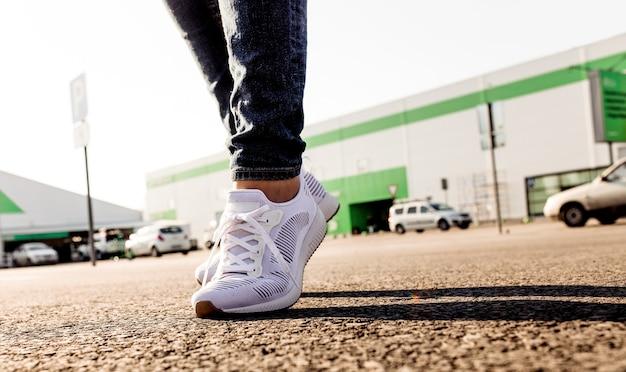 太陽に向かってアスファルト道路に立っている白いスニーカーの女性、クローズアップ。