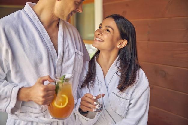 남자가 오렌지 레모네이드를 손에 들고있는 동안 그녀의 남자 친구에게 웃고 흰색 부드러운 목욕 가운에 여자