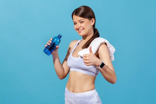 白いスポーツトップとタイツの女性がボトルからミネラルウォーターを飲み、親指を立てる