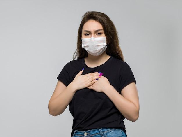 Женщина в белой стерильной медицинской маске чувствует себя плохо