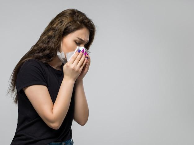 彼女の鼻を拭く白い滅菌医療防護マスクの女性