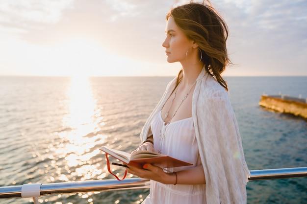 Женщина в белом летнем платье гуляет по берегу моря на восходе солнца с дневником в романтическом настроении думает и делает заметки