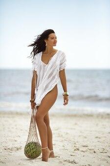 ビーチでスイカと白い夏のドレスの女性