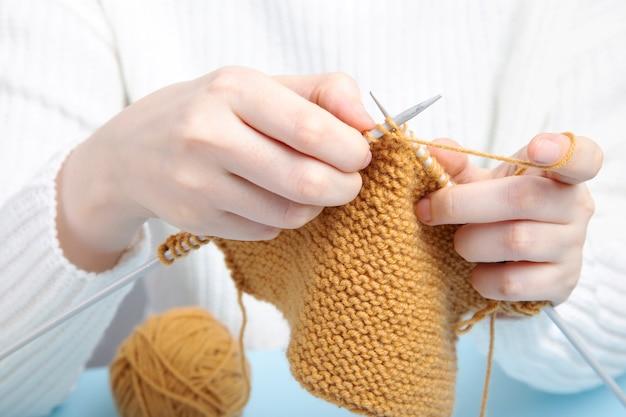 黄色い糸の服を編む白いセーターの女性
