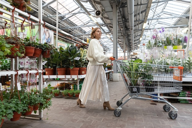 쇼핑 트롤리가 온실이나 정원 센터에서 그녀의 집을 위해 식물을 선택하고 구입하는 흰색 스웨터에 여자