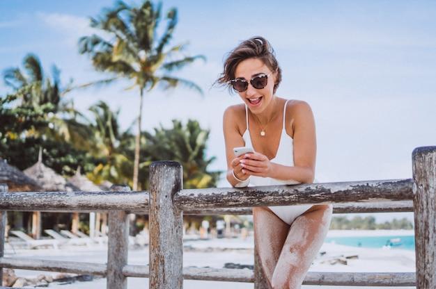 Женщина в белом купальнике на берегу океана с помощью телефона