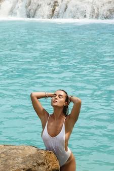 白い水着の女性が滝の横にある岩の上でポーズをとってください。