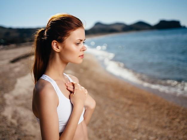 太陽の魅力をポーズビーチで白い水着の女性