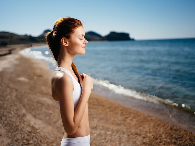 ビーチの海岸の海をポーズする白い水着の女性