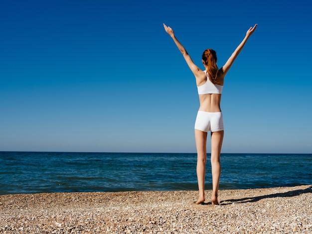白い水着の女性ヨガエクササイズビーチライフスタイル海