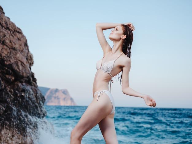 白い水着ファッションライフスタイル夏のビーチポーズの女性。高品質の写真
