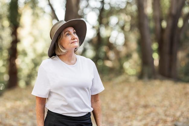 숲의 아름다움을 감상하는 흰색 티셔츠에 여자