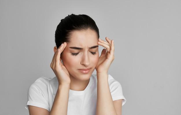 白いtシャツの女性は健康問題の頭痛をトリミングしました。