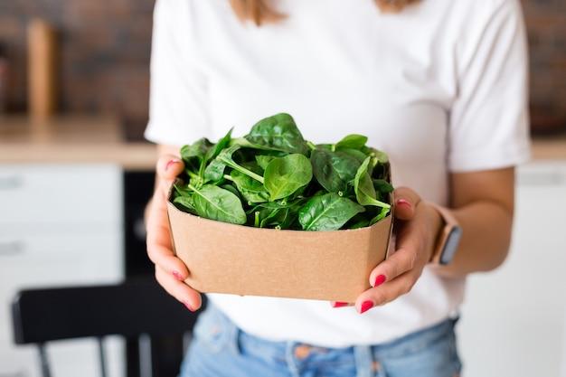 エコロジーパッキングのリサイクルで緑のほうれん草を保持している白いtシャツの女性。ローフードダイエットと健康的な食事のコンセプト。ベビーフード