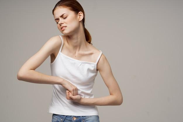 그녀의 배꼽 건강 문제 월경 산부인과를 들고 흰색 티셔츠에 여자