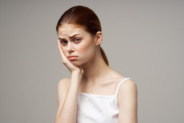 白いtシャツの女性は所有者の歯痛感情モデルの手を握ります
