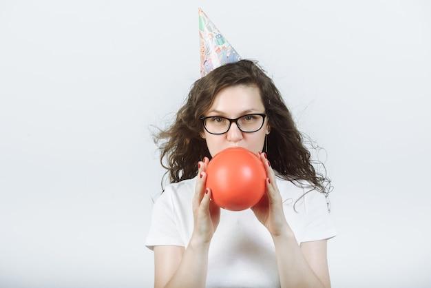 안경 및 파티 모자와 흰색 티셔츠에 여자가 팽창하거나 회색에 빨간 풍선을 날려