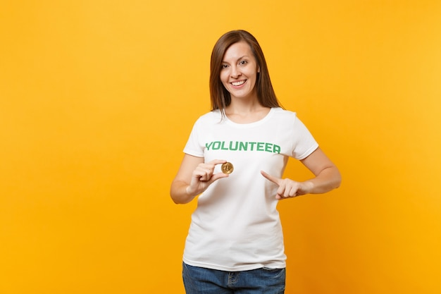흰색 티셔츠에 녹색 제목 자원봉사자가 적힌 여성은 노란색 배경에 격리된 비트코인, 금속 동전 미래 통화를 보유하고 있습니다. 자발적인 무료 지원 도움, 자선 은혜 작업 개념
