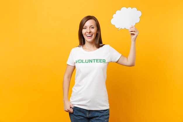 書かれた碑文の緑のタイトルボランティアと白いtシャツの女性は、黄色の背景に分離された空の空白のセイクラウド吹き出しを保持します。自発的な無料支援は、チャリティーグレースワークのコンセプトを支援します。