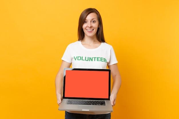 흰색 티셔츠를 입은 여성은 녹색 제목 자원 봉사자가 노트북 pc 컴퓨터를 들고 노란색 배경에 격리된 빈 화면을 들고 있습니다. 자발적인 무료 지원 도움, 자선 은혜 작업 개념.