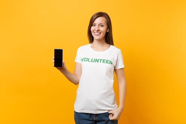 흰색 티셔츠를 입은 여성은 녹색 제목 자원봉사자가 노란색 배경에 격리된 빈 화면이 있는 휴대전화를 들고 있습니다. 자발적인 무료 지원 도움, 자선 은혜 작업 개념.