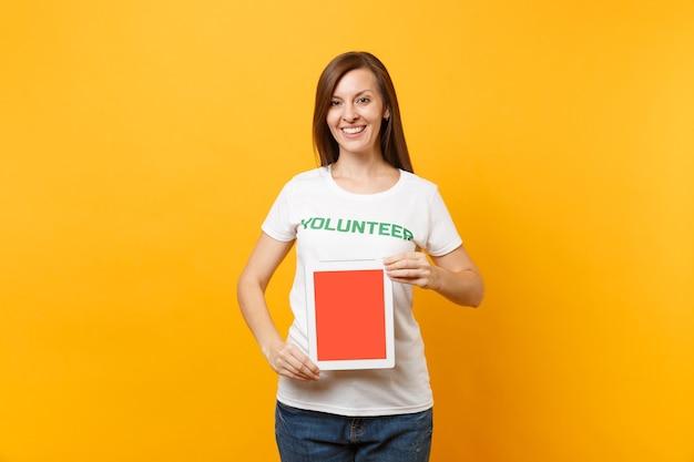 흰색 티셔츠를 입은 여성은 녹색 제목 자원 봉사자가 태블릿 pc 컴퓨터를 들고 노란색 배경에 격리된 빈 화면을 들고 있습니다. 자발적인 무료 지원 도움, 자선 은혜 작업 개념.