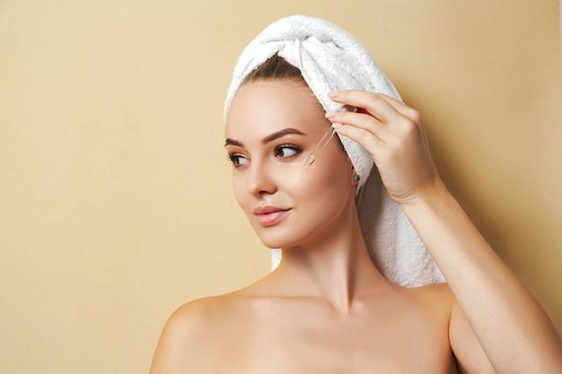 Женщина в белом полотенце наносит сыворотку на лицо