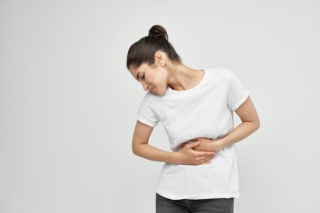 Женщина в белой футболке лечение боли в животе от дискомфорта