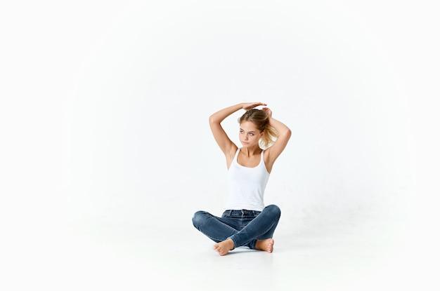 흰색 티셔츠와 청바지를 입은 여성은 바닥 조명 배경 스튜디오 모델에 앉아 있습니다.