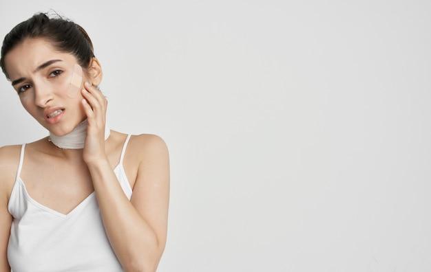 首の明るい背景に白いtシャツ包帯の女性