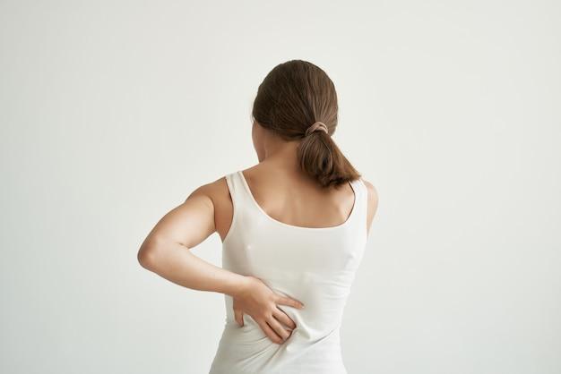 白いtシャツの女性体の痛み慢性疾患薬の症状