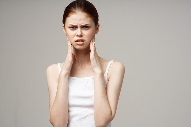 頭の片頭痛障害孤立した背景を保持している白いtシャツの女性