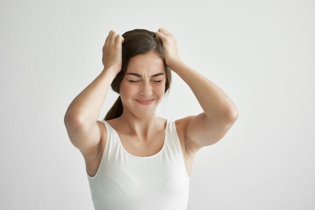 彼女の頭の頭痛の感情のライフスタイルのうつ病を保持している白いtシャツの女性
